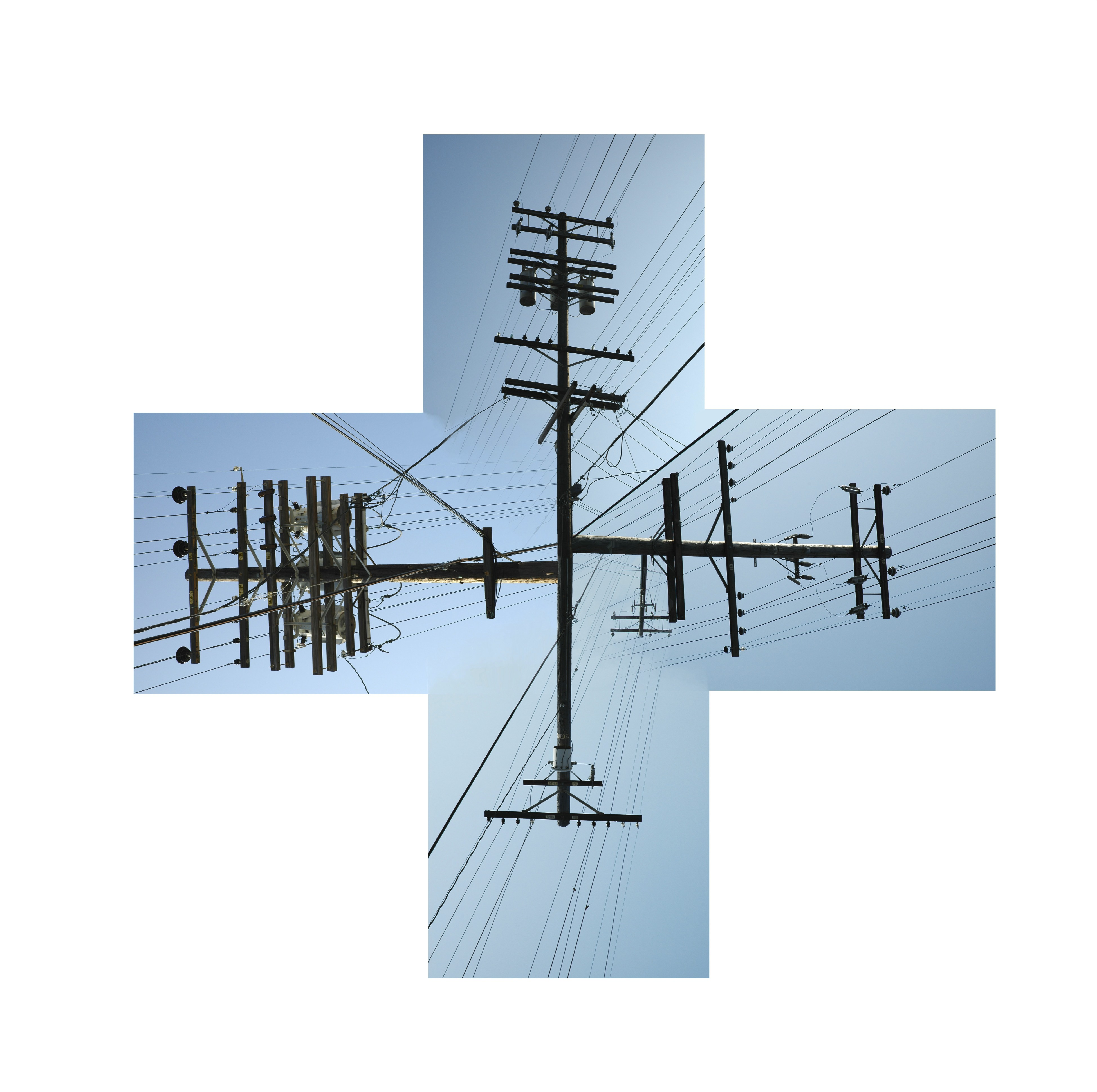 four utility poles in a medical cross